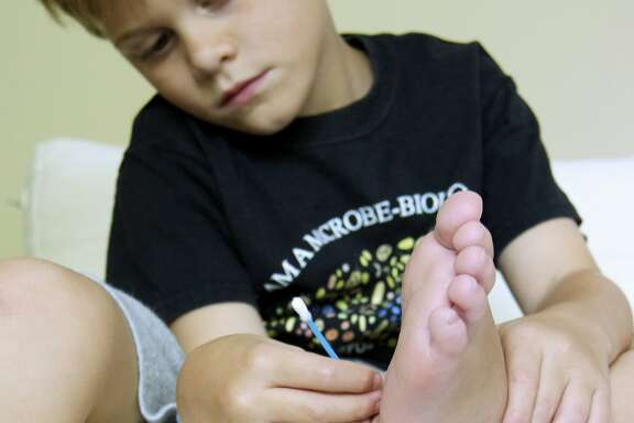 In this undated photo provided by the Gilbert family shows Dylan Gilbert, 7, of Naperville, Ill., demonstrating how he helped collect samples of bacteria from his foot during a 2012 study. Dylan's father, microbiologist Jack Gilbert of Argonne National Laboratory, led the Home Microbiome Project that analyzed bacteria in seven homes around the country, including his own, and found the microbes that normally live in people's bodies quickly move onto their doorknobs, countertops and floors. (AP Photo/Gilbert Family)