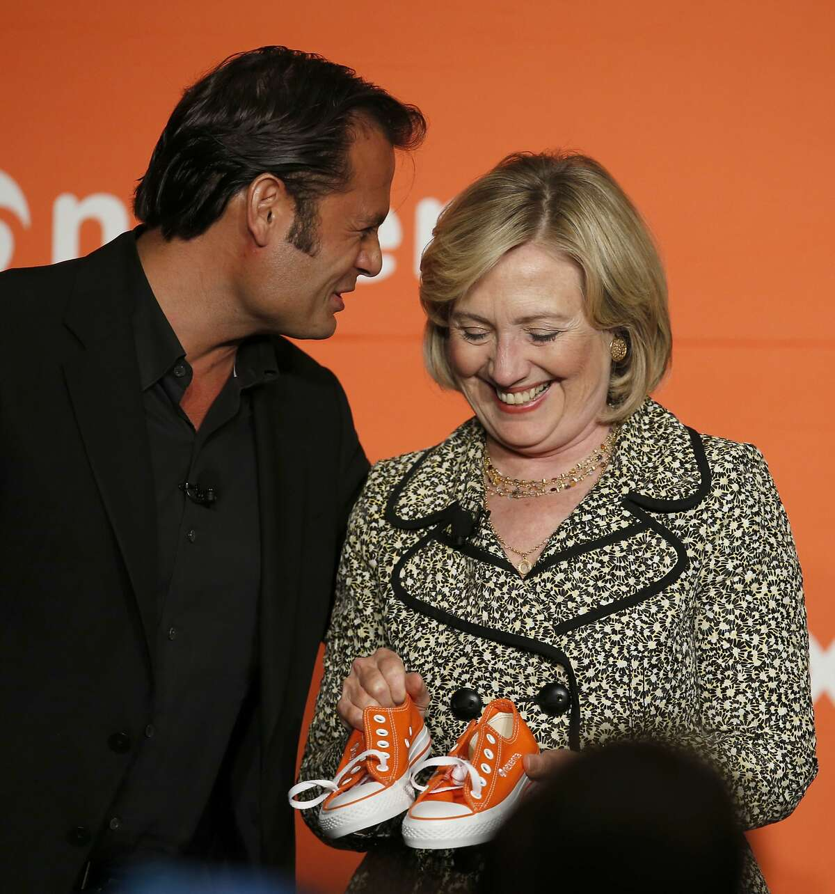 Tarkan Maner, CEO of Nexenta presented a pair of orange tennis shoes, in the color of his company, to former Secretary of State Hillary Rodham Clinton following a fireside chat during the Nexenta OpenSDx Summit at the St. Regis Hotel in San Francisco, Calif., on Thursday Aug. 28, 2014.