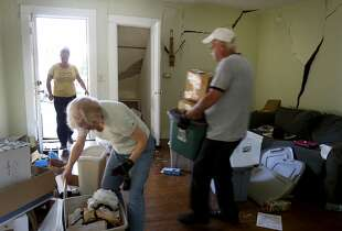Sarah Sandbeck (left) is helped by her parents Kaye and Bob Kinsey to move out of her red tagged home on Fourth Street Monday August 25, 2014. Residents and shop owners in Napa, Calif. spent the day cleaning up or moving out after the large earthquake Sunday.