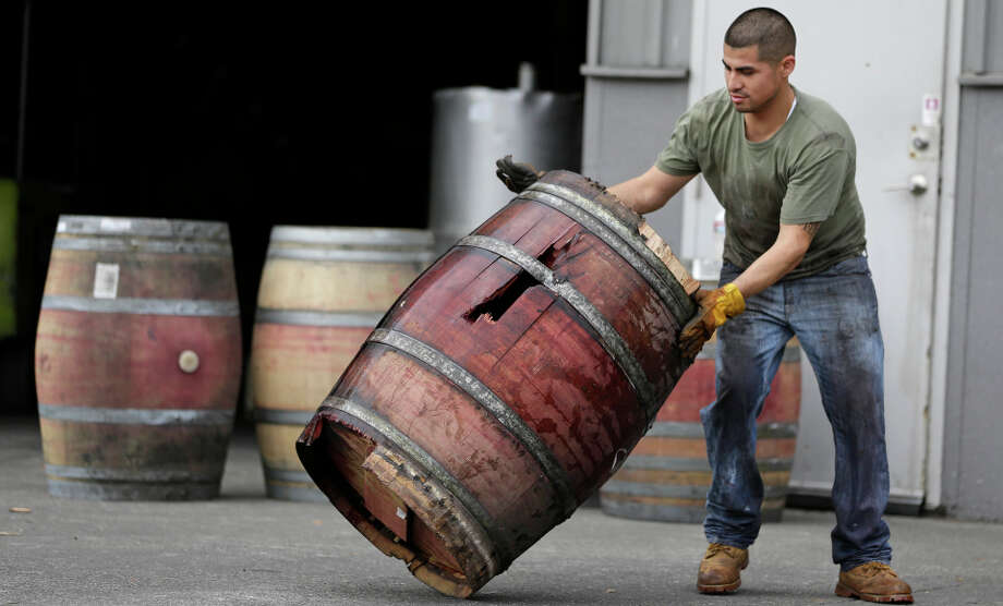 A worker removes an earthquake-damaged wine barrel from Napa Barrel Care Monday, Aug. 25, 2014, in Napa, Calif. A powerful earthquake that struck the heart of California's wine country caught many people sound asleep, sending dressers, mirrors and pictures crashing down around them and toppling wine bottles in vineyards around the region. The magnitude-6.0 quake struck at 3:20 a.m. PDT Sunday near the city of Napa. (AP Photo/Eric Risberg) Photo: Eric Risberg, STF / Associated Press / AP