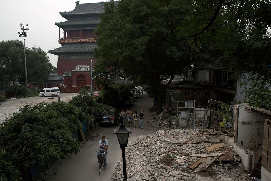 A man cycles past demolished hutongs or alleyways that dated back to 1272 in Beijing. Modern structures and roads have replaced some 60 percent of the inner core of the city. Photo: Ng Han Guan, Associated Press