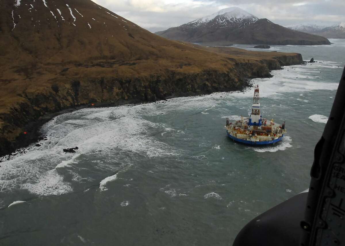 In this image provided by the U.S. Coast Guard shows two life rafts sit on the beach adjacent as the conical drilling unit Kulluk sits grounded 40 miles southwest of Kodiak City, Thursday, Jan. 3, 2012. The Kulluk grounded after many efforts by tug vessel crews and Coast Guard crews to move the vessel to safe harbor during a winter storm.Calls for federal scrutiny of Royal Dutch Shell PLC drilling operations in Arctic waters swelled Thursday with a request for a formal investigation by members of Congress. (AP Photo/U.S. Coast Guard, Petty Officer 2nd Class Zachary Painter)