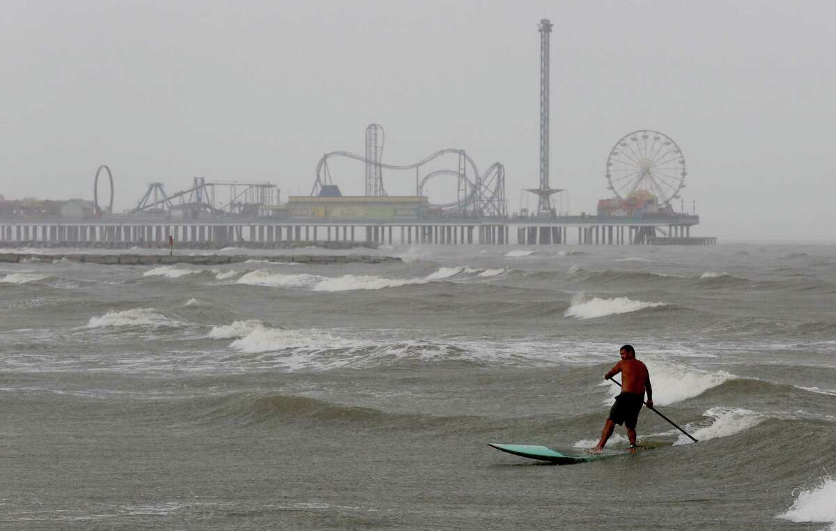 Paddle boarder Ertic Bingham, from Sugarland braves the weather as he surfs the waves on August 28, 2014 on Galveston Beach in Galveston, TX.