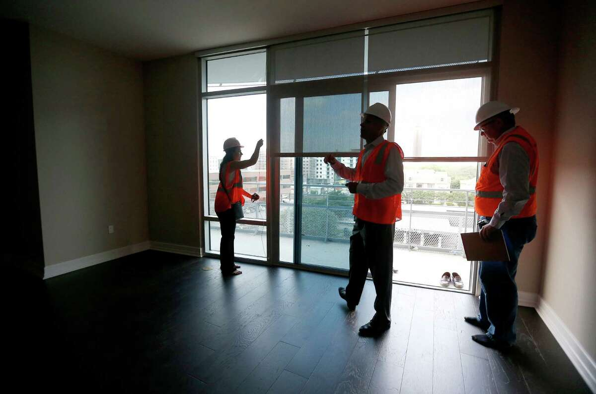 Misty Meredith, with leasing, Roger Gregory, President of Investments, and Tony Martin VP of construction, stand inside one of the nearly completed units at the 40-story residential high-rise under construction at 2929 Weslayan, Thursday, Aug. 28, 2014, in Houston. ( Karen Warren / Houston Chronicle )