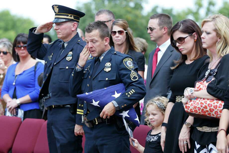 Oklahoma City police officer Sgt. Ryan Stark, center, wipes a tear from his eye following funeral services for his canine partner, K-9 Kye, in Oklahoma City, Thursday, Aug. 28, 2014.  Photo: Sue Ogrocki, Associated Press / AP