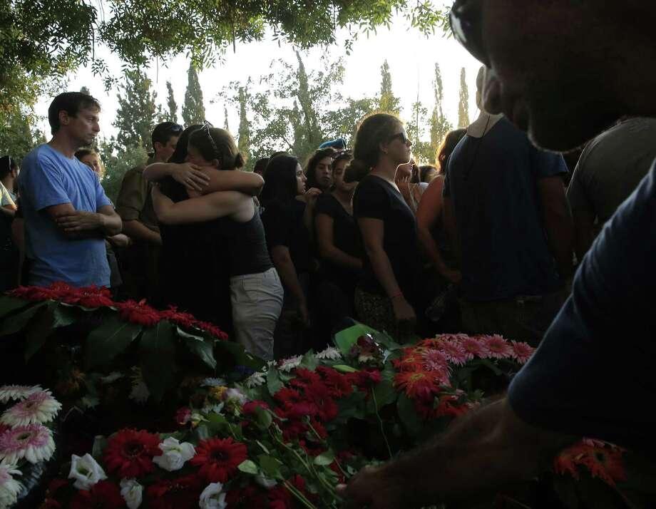 Friends and relatives mourn Ze'evik Etzion, a 55-year-old officer who was killed by a Palestinian mortar shell in Kibbutz Nirim near the Israel-Gaza border. Photo: Tsafrir Abayov / Associated Press / AP