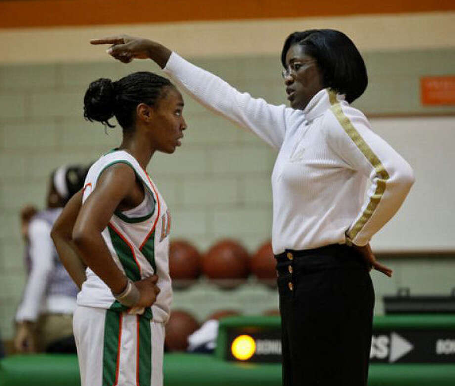 Milyse Lamkin coaches Shatia Bartlett in a 2009 game against Poteet at Sam Houston High School. Lamkin has died at 52. Photo: Lisa Krantz / San Antonio Expres