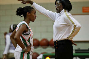Girls varsity basketball coach and Sam Houston alum Milyse Lamkin coaches senior Shatia Bartlett during their game against Poteet at the school on Tuesday, December 15, 2009.