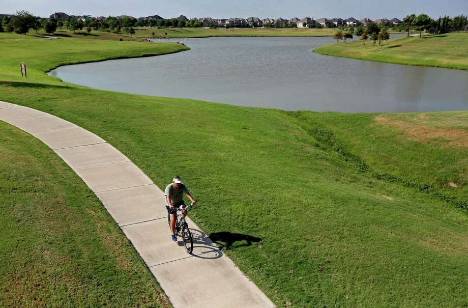 This is a dry detention area  in Houston's Cinco Ranch development, which is landscaped with greenbelt trails, trees, shrubs and some water to turn them into recreational and scenic amenities for the community. Photo: Gary Coronado, Houston Chronicle / © 2014 Houston Chronicle