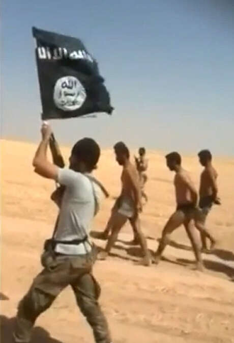 An image from a video uploaded on social networks on Thursday shows men being marched along a desert road before apparently being killed en masse by Islamic State militants. Photo: Getty Images / AFP