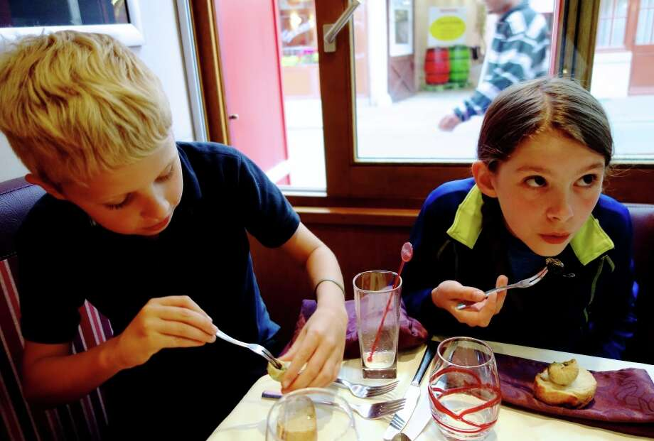 Travelers of all ages — here trying snails for the first time — can reach new gastronomic heights in France. RS14Spring_830.jpg Photo: Rick Steves / ONLINE_YES