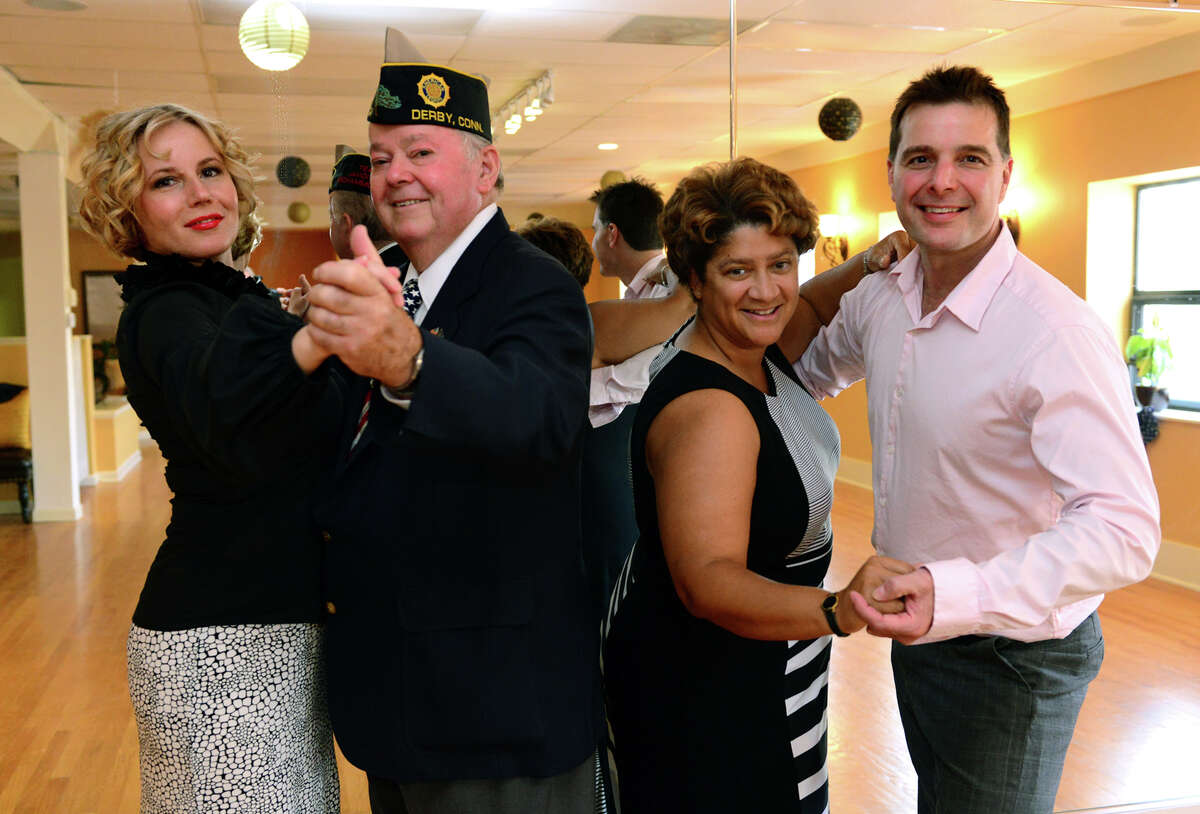 """Fred Astaire Dance Studio owners and professional dancers Monika Barska, left, and Henry Skopp, right, pose with their dance partners, Korean War-era veteran Gus Williams and Operation Iraqi Feedom veteran Eunice Ramirez at the studio in Southport, Conn. on Thursday August 28, 2014. The Fred Astaire pros are teamed up with these veterans to take part in the """"Dancing With Our Heroes"""" event in Hartford on September 13, 2014. The dance will help raise money to build a Fisher House at the VA in West Haven."""