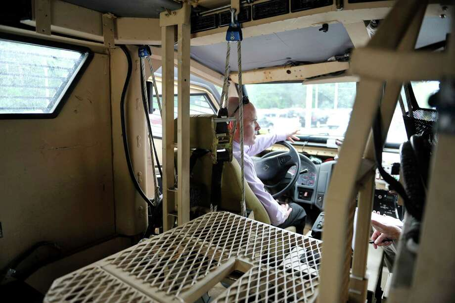 Shawn Noonan, an investigator with the  Albany County Sheriff's office and a member of the Sheriff's Emergency Response Team, sits inside a former military vehicle on Wednesday, Aug. 27, 2014, in Colonie, N.Y.  The vehicle was obtained last fall under a program by the U.S. Defense Department to provide surplus military equipment to local police forces.   (Paul Buckowski / Times Union) Photo: Paul Buckowski / 00028349A