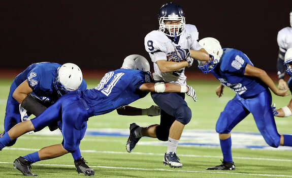 Central Catholic's Jimin Suh looks for running room around Lanier's Juan Palomino during second half action Thursday Aug. 28, 2014 at Alamo Stadium. Central Catholic won 30-0. Photo: Edward A. Ornelas, San Antonio Express-News / © 2014 San Antonio Express-News