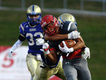 Lumberton's Tim Rhodes, No. 7, is tackled along the sideline by Hamshire-Fannett's Jeremiah Hargraves, No. 27, on Thursday night. The Hamshire-Fannett Longhorns opened their season Thursday night against the Lumberton Raiders at Provost Umphrey Stadium. Photo taken Thursday 8/28/14 Jake Daniels/@JakeD_in_SETX