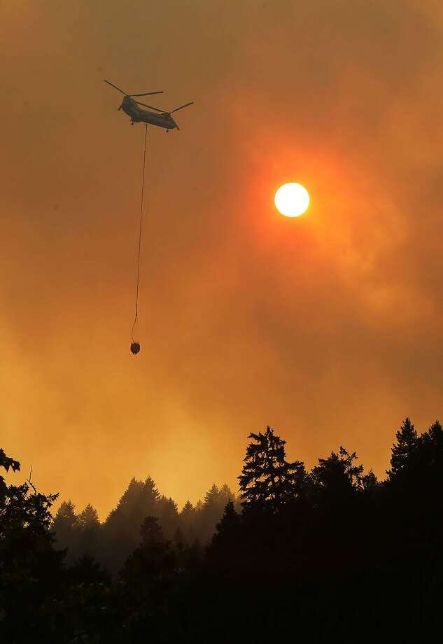 A helicopter brings water to the east flank of the Deception Complex Fire near Oakridge, Ore. Thursday Aug. 28, 2014 as the sun sets behind a burning ridgeline near Highway 58. (AP Photo/The Register-Guard, Chris Pietsch) Photo: Chris Pietsch, Associated Press