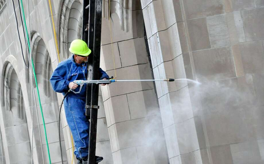 Glenn Miller, a restoration specialist with Spec Restoration Company, uses a power washer to clean the masonry on the front of the former Traders Bank building Thursday, Aug. 28, 2014, as work continues on the future corporate headquarters of DBi Services located at the intersection of East Broad and Wyoming streets in Hazleton, Pa. (AP Photo/Hazleton Standard-Speaker, Ellen F. O'Connell) Photo: Ellen F. O'Connell, Associated Press