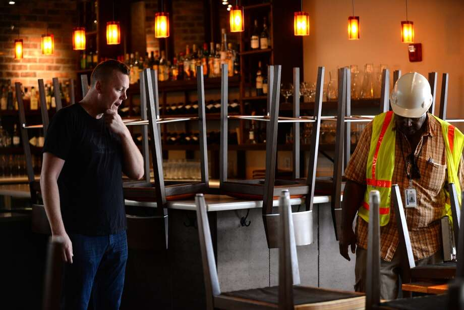 Tyler Rodde, left, owner of Oenotri restaurant in downtown Napa with City of Napa building inspector Keith Marks looking over some floor damage from the Sunday morning 6.0 quake. Rodde was relieved to be allowed to open up for dinner service that evening with the only restriction being no allowed outdoor seating. August 25, 2014. Photo: Erik Castro, Special To The Chronicle