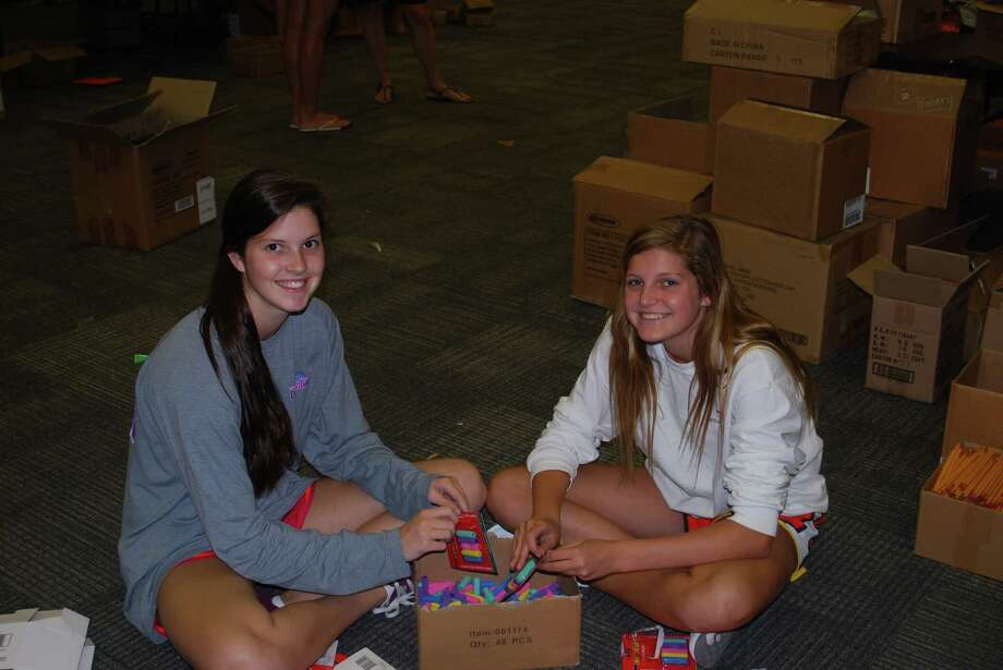 Claire and Kelly Tate, respectively a junior and freshman from Memorial High School, assemble pencil pillows for the 2014 SBEF School Supply Drive. Photo: Spring Branch Education Foundati