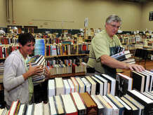 Volunteers Sandi O'Reilly and Thom Field sort books as they and others prepare for the 54th Annual Mark Twain Library Book Fair, at the Redding Community Center in Redding, Conn. Aug. 28, 2014. The fair opens Friday morning, and continues from 9am through 4pm each day until Monday.