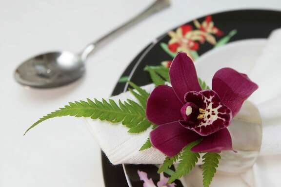 Orchid used to dress up napkin ring and orchid dinnerware are photographed at the home of Jane Malin   on Wednesday, Aug. 20, 2014, in Clear Lake. ( J. Patric Schneider / For the Chronicle )