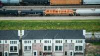 Rail tank cars are seen on tracks behind new homes under construction in the Cottage Grove area on Wednesday, Aug. 20, 2014, in Houston. Transport of crude oil by rail has become increasingly common, raising safety concerns after a series of derailments around the country. ( Smiley N. Pool / Houston Chronicle )