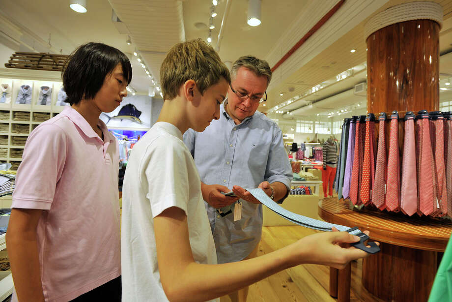 Michael Mrozek, of Greenwich, looks at a tie with his son, Jan, center, a 13-year-old attending Central Middle School, with Jan's friend, Stephen Ryan, a twelve-year-old from North Andover, Mass., who will be attending seventh grade at Learning Prep School, while shopping at Vineyard Vines during the start of tax-free week for school shopping in Greenwich. Photo: Jason Rearick / Stamford Advocate