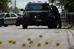 Markers (bottom, foreground) show where bullet shell casings landed on the 600 block of Corliss on the East Side Friday August 29, 2014. San Antonio Police Chief William McManus said two males on foot used two handguns to fire 28 rounds into the home on Corliss striking a male victim in his early 20s. The victim was transported to San Antonio Military Medical Center.