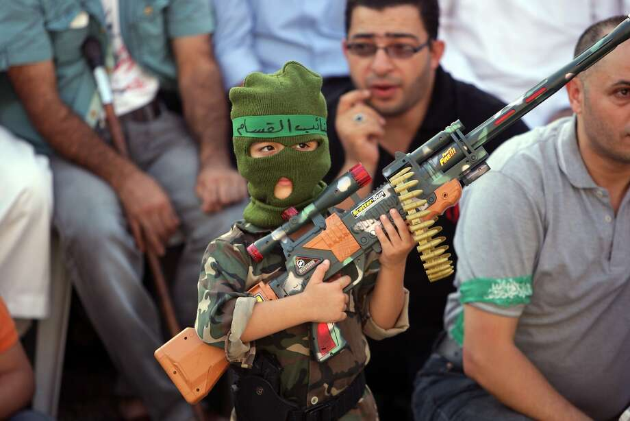 A Palestinian boy holds a toy gun during a celebration organized by Hamas in the West Bank city of Nablus, on Friday, Aug. 29, 2014.    Israel and Hamas militants fought for 50 days before reaching a truce on Tuesday.  Palestinian President Mahmoud Abbas has accused Hamas of needlessly extending fighting in the Gaza Strip, causing a high death toll. (AP Photo/Nasser Ishtayeh) Photo: Nasser Ishtayeh, Associated Press