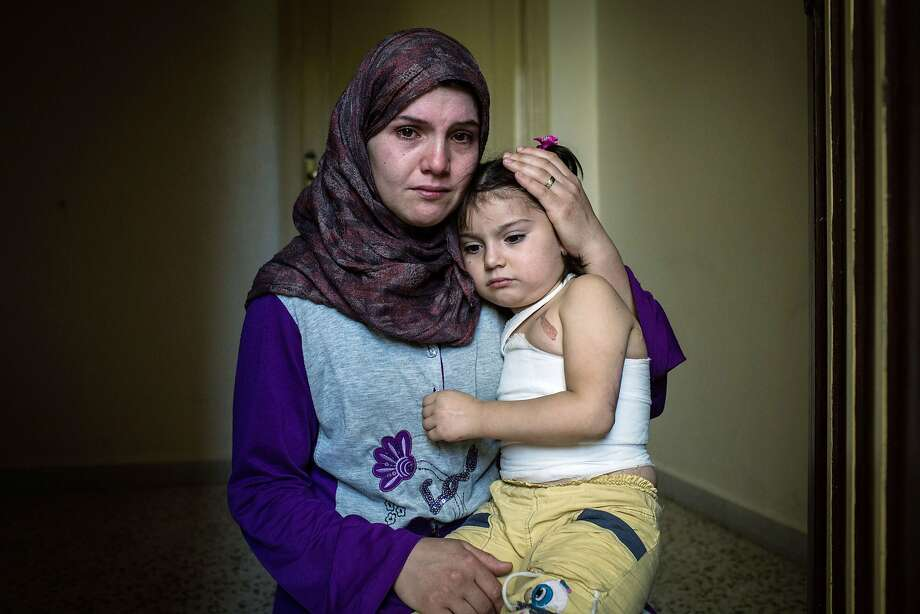 Dayane, 24, holds her daughter Yemen, 5, at a refugee camp in northern Lebanon. Yemen was badly burned in a bombing raid in Yarbroud, Syria. Photo: Andrew Mcconnell, AFP/Getty Images