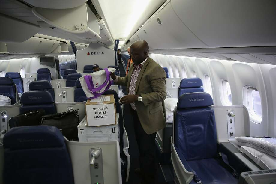 MONROVIA, LIBERIA - AUGUST 13:  Liberian Foreign Affairs Minister Augustine Ngafuan hand-carries boxes an experimental Ebola-fighting drug ZMapp on a Delta Airlines flight from New York's JFK airport to Monrovia on August 13, 2014 in Monrovia, Liberia. The Liberian government says the drug is meant to be used to treat Liberian doctors infected by the deadly virus which has killed more than 1,000 people in four West African countries.  (Photo by John Moore/Getty Images) *** BESTPIX *** Photo: John Moore, Getty Images