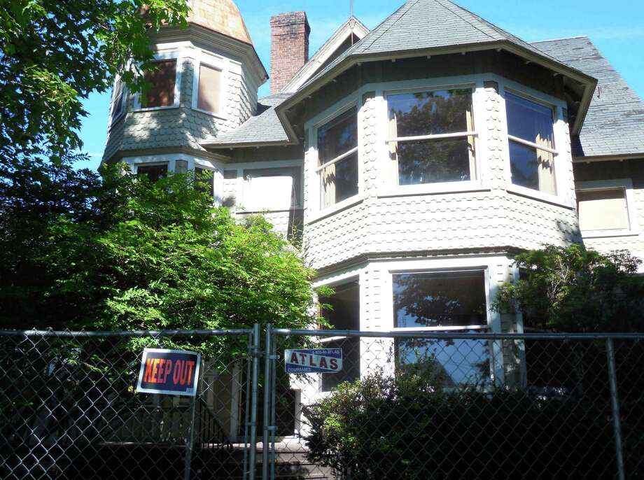 The 130-year-old, Queen Anne-style Kemper-Gunn house on Church Lane has been fenced-off and some of the original stained glass windows, including those in an upstairs attic space, have been removed and the window spaces boarded up. The house is being moved from its current location to the nearby Baldwin parking lot . Photo: Anne M. Amato / westport news