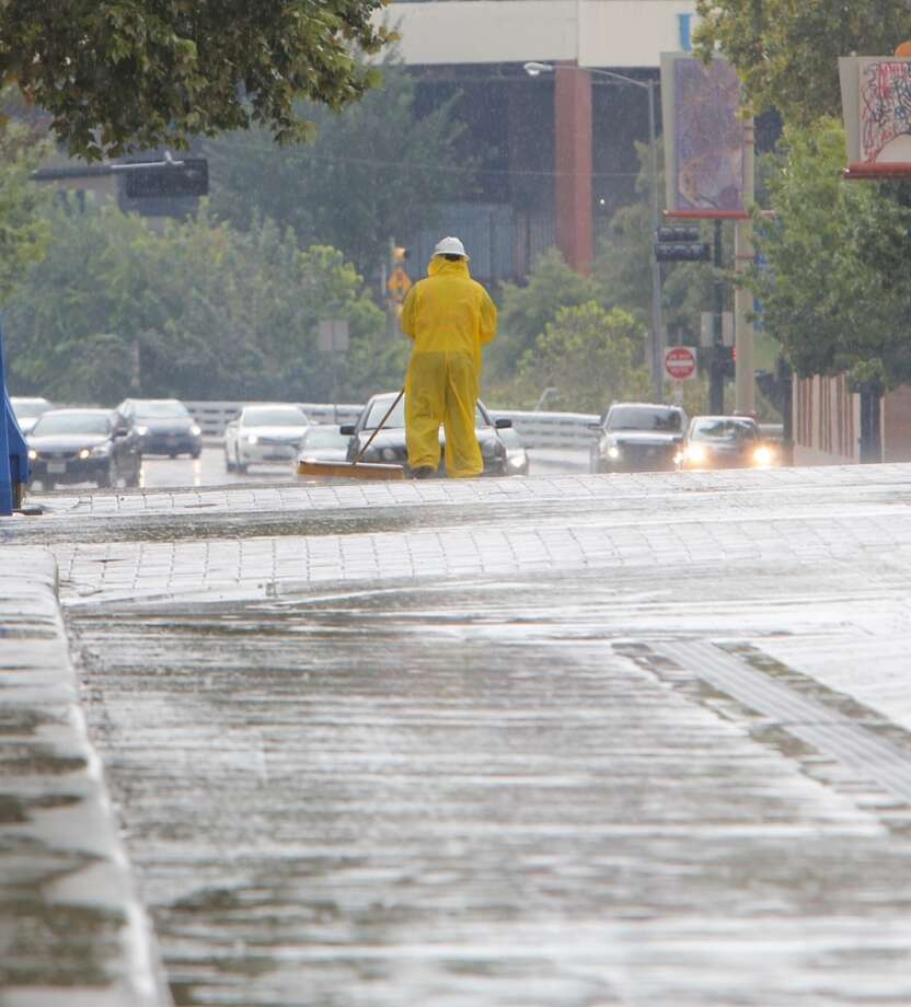 Construction workers sweep mud from the street at a job site at Milam and Preston streets during a rain shower. Photo: James Nielsen, Houston Chronicle