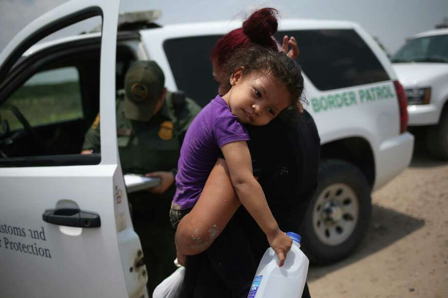 MISSION, TX - JULY 24:  A mother and child, 3, from El Salvador await transport to a processing center for undocumented immigrants after they crossed the Rio Grande into the United States on July 24, 2014 in Mission, Texas. Tens of thousands of immigrant families and unaccompanied minors have crossed illegally into the United States this year and presented themselves to federal agents, causing a humanitarian crisis on the U.S.-Mexico border.  (Photo by John Moore/Getty Images) ORG XMIT: 502714825 Photo: John Moore / 2014 Getty Images
