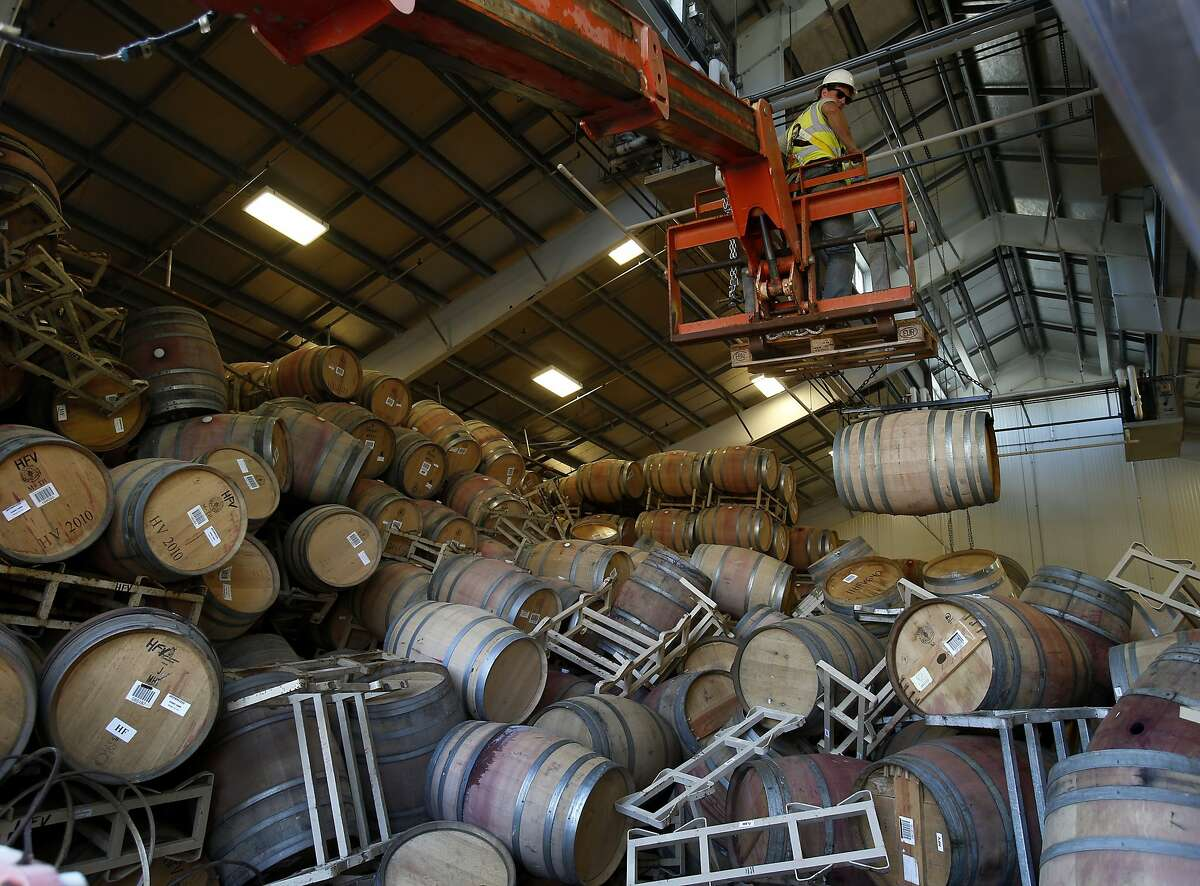 A work crew using a fork lift and a special harness started the process of bringing out hundreds of fallen wine barrels from Starmont Winery Wednesday August 27, 2014. Some southern Napa Valley wine makers were hit hard by the recent earthquake, but cleanup has been steady and 95 percent are now back in business.