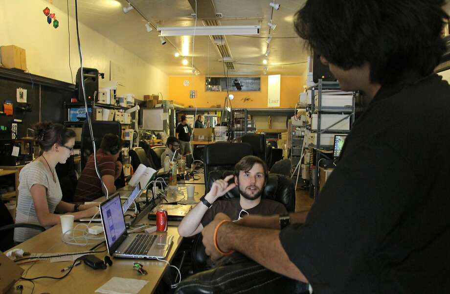 People talk and work on computers at a communal workbench at HeatSync Labs in Mesa, Ariz. The nondescript garage-like space is where inventors and tinkerers can work on projects and share ideas. Photo: Emaun Kashfi, Associated Press