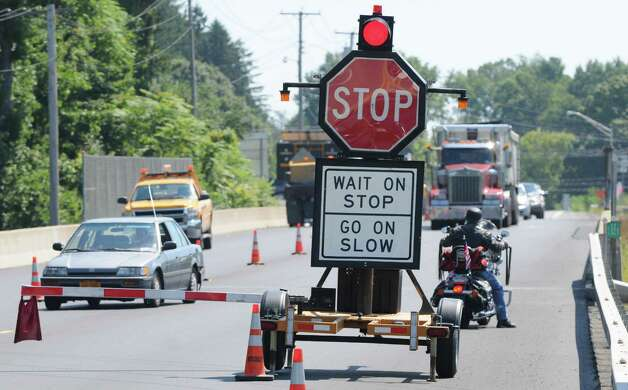 A mechanical flagger manages traffic around a road construction site Monday, Aug. 25, 2014, on Route 23 in Catskill, N.Y. The motorcyclist at right road past the stop sign and then stopped after it. (Will Waldron/Times Union) Photo: WW / 00028309A