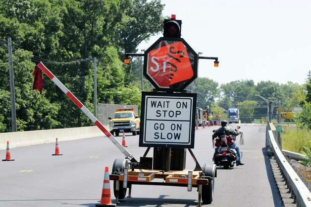 The arm of a mechanical flagger is raised and its sign turns from stop to slow as it manages traffic around a road construction site Monday, Aug. 25, 2014, on Route 23 in Catskill, N.Y. The motorcyclist at right road past the stop sign and then stopped after it. (Will Waldron/Times Union) Photo: WW / 00028309A