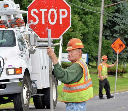 Jack Schloss, center, of Mechanicville flags traffic on Heritage Lane as crews string fiber optic cable Friday August 15, 2014, in Colonie, NY.  (John Carl D'Annibale / Times Union) Photo: John Carl D'Annibale