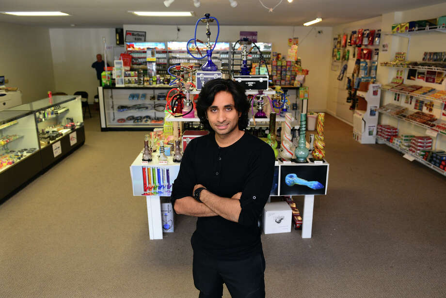 Syed Naqvi, owner of Smoke and Print Universe poses inside the store on Main Street in Bridgeport, Conn. on Wednesday July 16, 2014. Naqvi is planning on turing the left half of the store into a hookah lounge. Photo: Christian Abraham / Connecticut Post