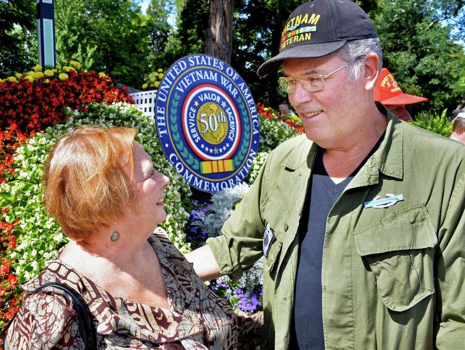 Manfred Spikereit of Glenville poses for a photo with his wife Mary at the Saratoga Springs Vietnam War 50th Anniversary Commemorative Committee's floral display created by the city's Public Works Department in Congress Park Friday Aug. 29, 2014, in Saratoga Springs, NY. Manfred served in the US Army's 52nd Infantry Div. in Vietnam in 1966-67.  (John Carl D'Annibale / Times Union) Photo: John Carl D'Annibale / 00028342A
