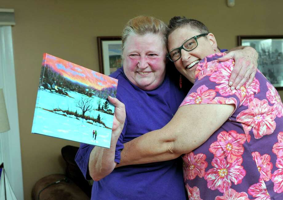 Patty Shanley Zelle, 56, right, will be undergoing stem cell treatment. Wednesday her sister Mary gave her a gift - a photo of a larger painting that she made for her sister. They are photographed in Zelle's Brookfield, Conn. home, Wed., Aug. 27, 2014. Photo: Carol Kaliff / The News-Times