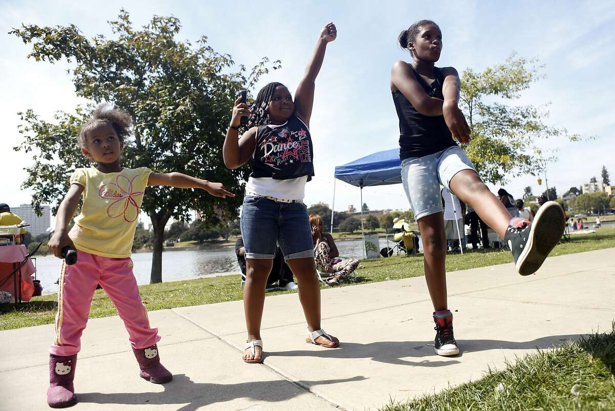 (left to right) Madison Gibson, 5; Taylor Blackmon, 10; and Janelle Crew, 11; dance along to a video game playing on the GameZone Party Truck during a pop-up community picnic at Lake Merritt in Oakland, Calif. on Sunday, August 3, 2014.