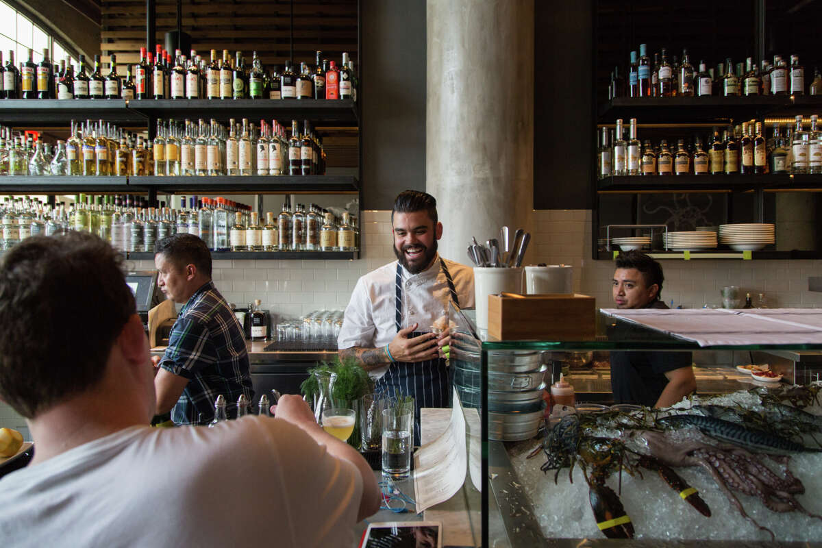 Sous chef Joey Malim mingles with patrons at the bar while shucking oysters at the raw bar at Jack's Oyster Bar and Fish House in Oakland.