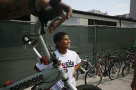 Eric Austin, 12, smiles as bike mechanic David Boone from The Bay Area BikeMobile does a tune-up on his bike at the Salesian Boy's and Girl's Club in San Francisco, Calif.