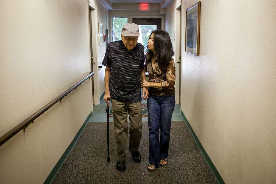 "Suzanne Krieger walks her father, Robert Lau, 91, down the hall of his assisted living center in Sacramento.  He uses a ""smart pill"" that tracks whether he takes medication. Below: The patch helps transmit his information. Photo: Max Whittaker/Prime, Special To The Chronicle"