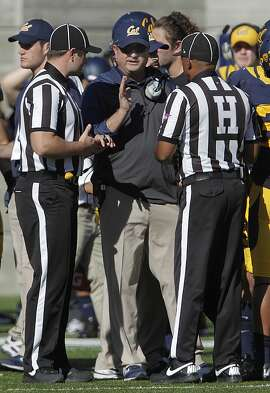 Cal head coach Sonny Dykes has a conference with officials during a timeout in the second quarter of the Cal Bears football game against the USC Trojans at Memorial Stadium in Berkeley, Calif. on Saturday, Nov. 9, 2013.