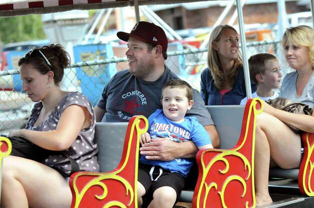 """Alex Fitzpatrick, 4, of Rotterdam, center, and his father, Josh Fitzpatrick, ride the train on Friday, Aug. 29, 2014, at Hoffman's Playland in Latham N.Y. Josh Fitzpatrick said he has wonderful memories of Hoffman's, and he's broken hearted that it will soon close. """"Such a loss,"""" he said. (Cindy Schultz / Times Union) Photo: Cindy Schultz / 10028400A"""