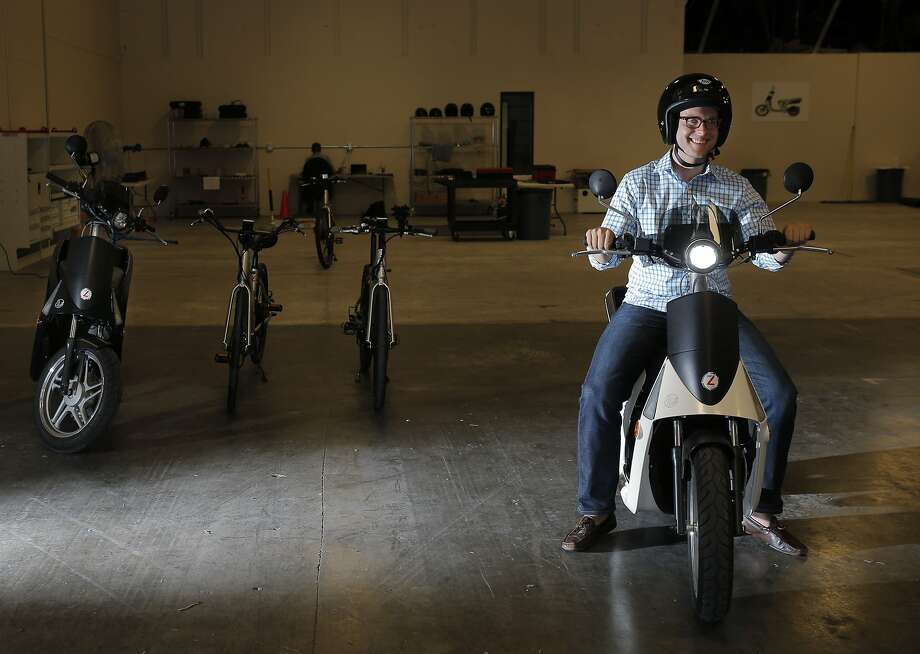 Alexander Boyce sits on a scooter at GenZe in Fremont. To the left of him are another scooter and two of the company's E-Bikes. Photo: Carlos Avila Gonzalez, The Chronicle