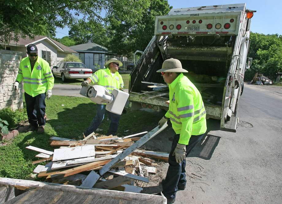In this photo from Tuesday May 20, 2008, Amos Castillo, center, throws a toilet into the City compactor truck as fellow Solid Waste workers, Marcus Rutledge, left.  (AP Photo/Austin American-Statesman, Larry Kolvoord) Photo: Larry Kolvoord, MBR / Austin American-Statesman